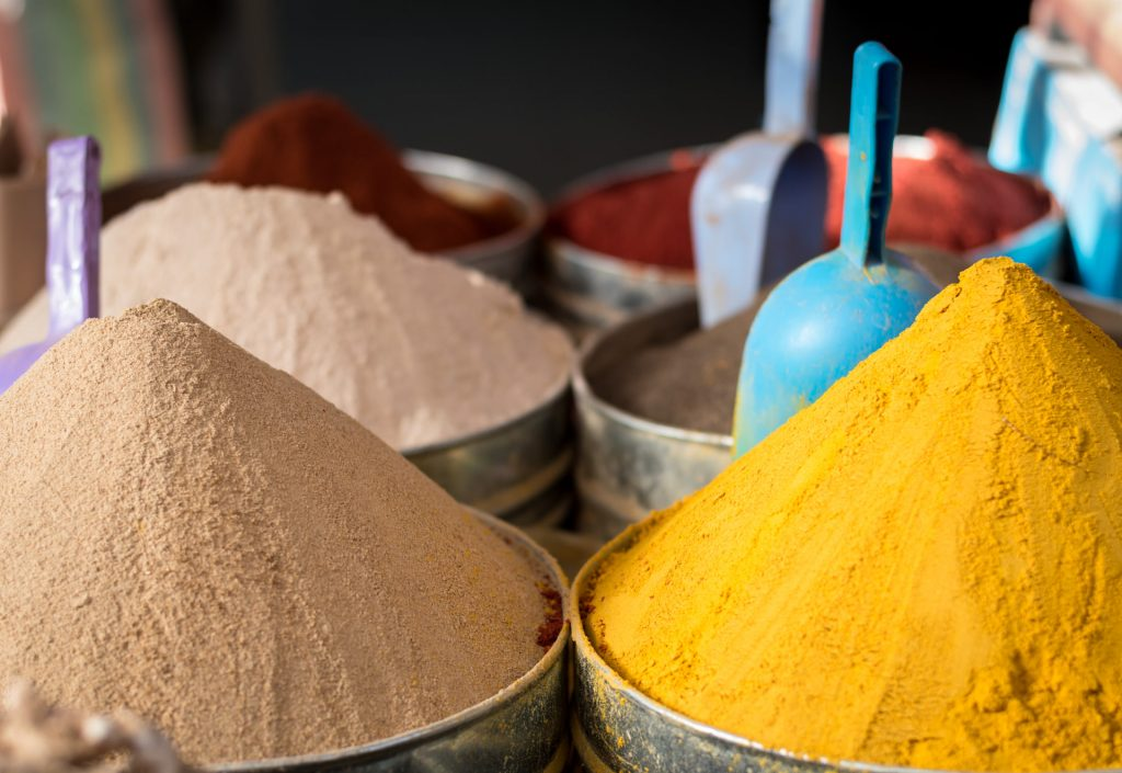 Closeup of large piles of vibrant and exotic, colourful spices in moroccan market, including turmeric and cumin.