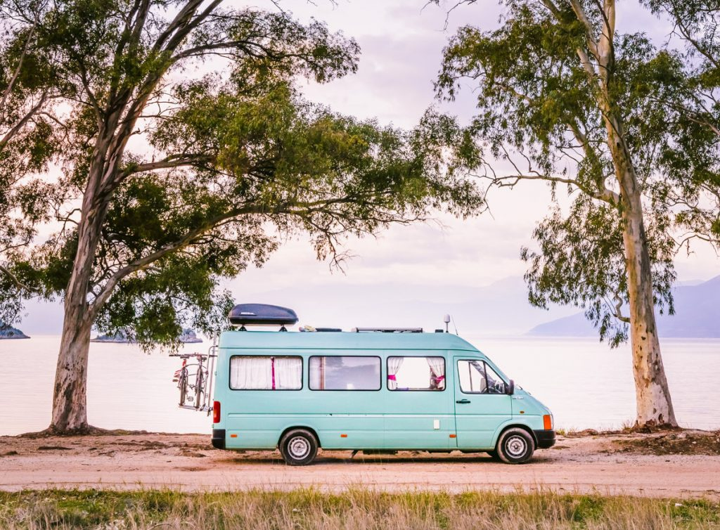 Camper van parked and framed between beautiful tall trees in evening light, with calm and serene sea  in the background.