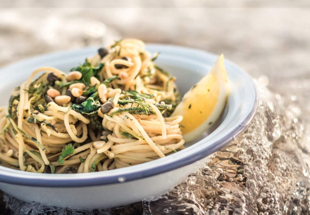 Gourmet Lemon, capers and dill spaghetti pasta bowl with pine nuts. Ocean waves splash over the dish for fresh concept.
