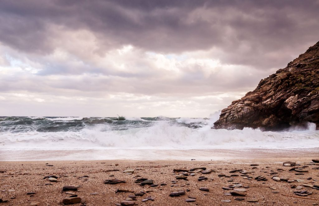 Big frothy waves crashing on a deserted, pepple beach in Greece. Jagged rocks and moody clouds in the sky create a dramatic scene.